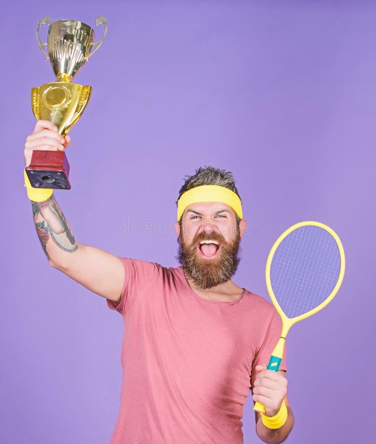 Celebri la vittoria Campione di tennis Racchetta di tennis atletica della tenuta dell'uomo e calice dorato Gioco di tennis di vit immagini stock libere da diritti