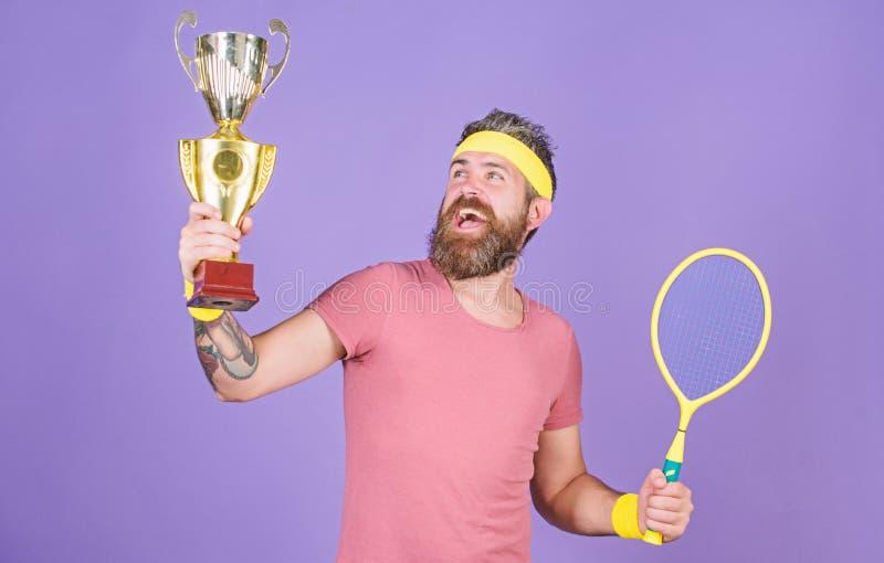 Celebri la vittoria Racchetta di tennis atletica della tenuta dell'uomo e calice dorato Campionato di vittoria del tennis Uomo ba fotografia stock