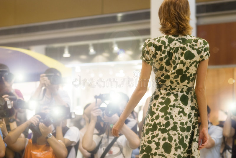 Celebrity. A model enjoying celebrity status as the camera flashes away at her