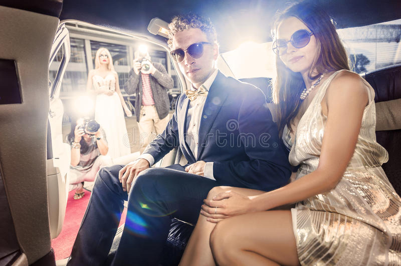 Celebrity couple in a limousine. Smartly dressed celebrity couple, ready to get out of a limousine during a red carpet event, with several paparazzi and tabloid stock photography