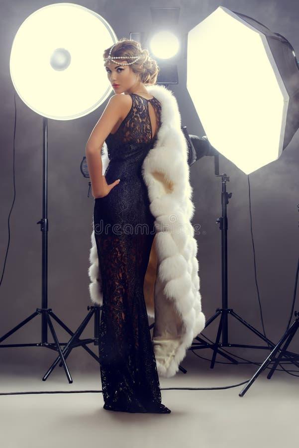 Celebrity. Stunning beauty model posing at studio in light flashes. Professional fashion model. Celebrity. Full length portrait stock photos