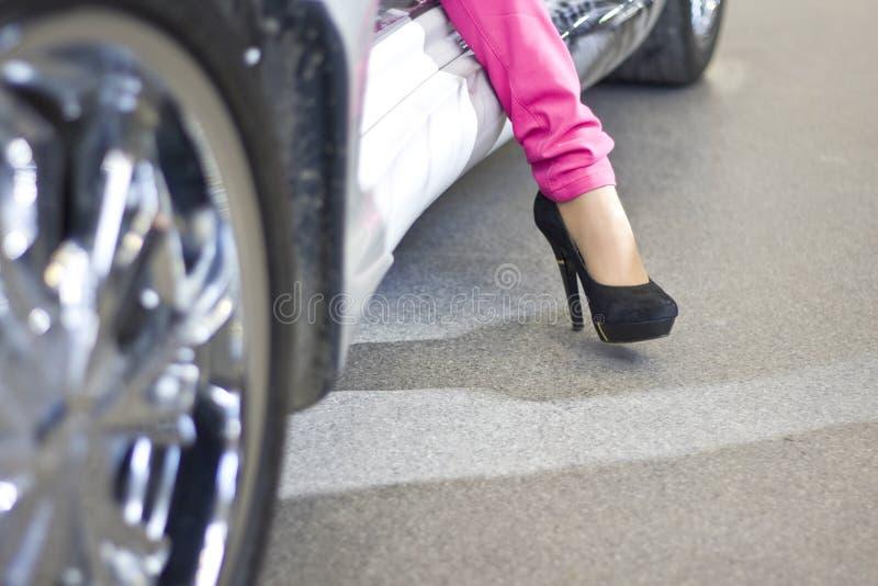 Celebrity woman exiting sportcar