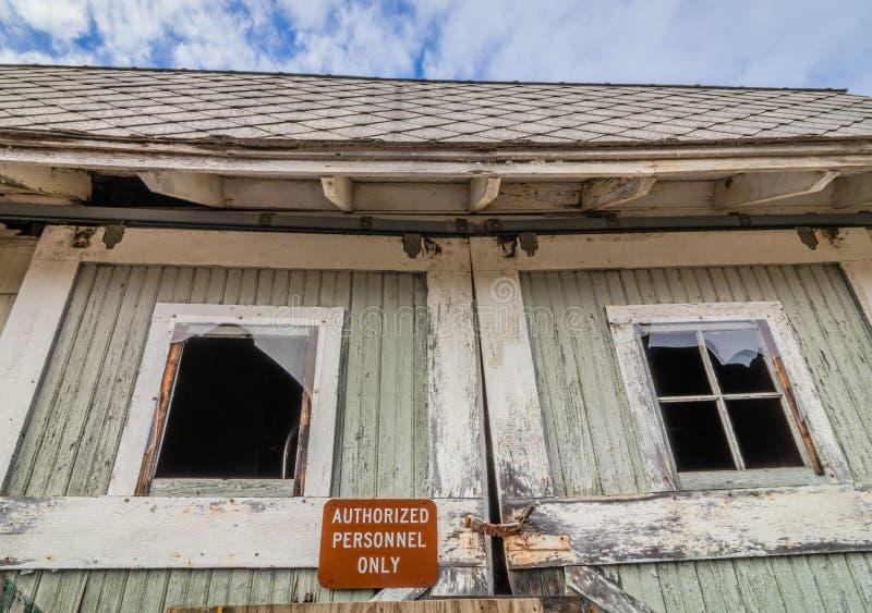 Celeiro abandonado rústico velho com sinal autorizado dos pessoais na porta com janelas quebradas fotos de stock