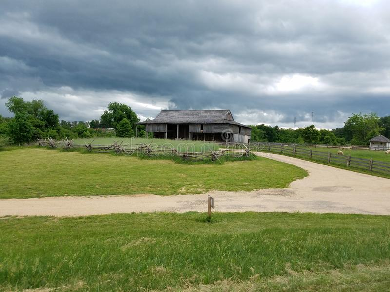 Celeiro de madeira velho na exploração agrícola com cerca e estrada e nuvens escuras foto de stock royalty free