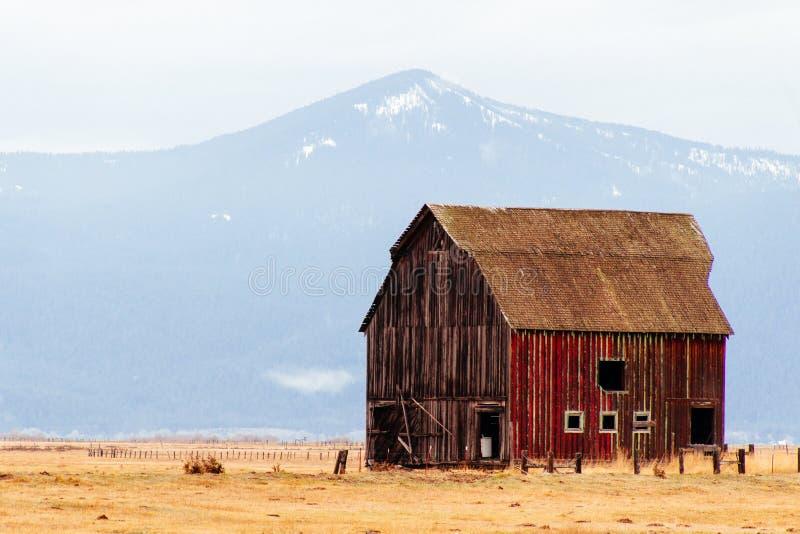 Celeiro de madeira vermelho em um grande campo com montanhas e montes no fundo fotografia de stock