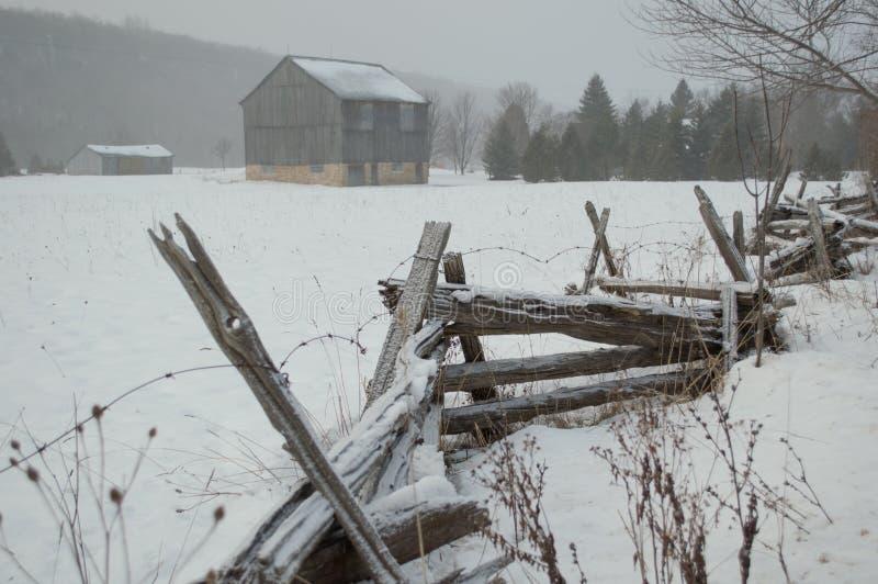 Celeiro e cerca rústicos no inverno imagens de stock royalty free