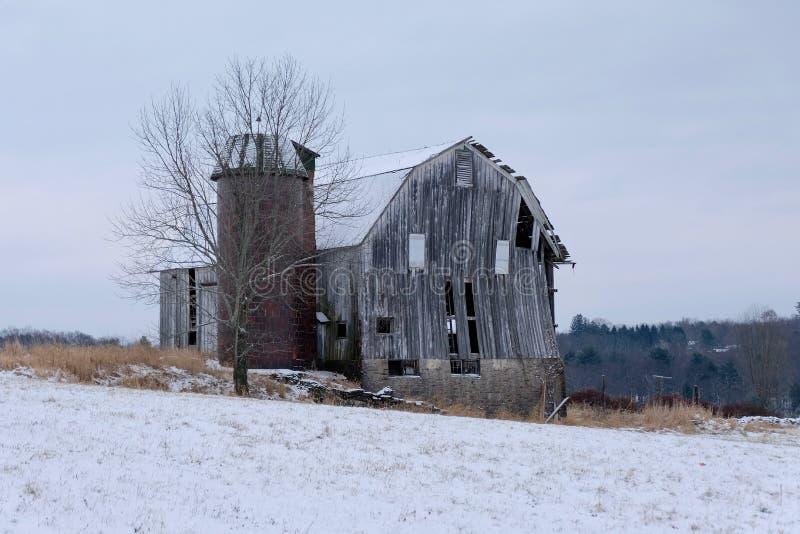 Celeiro e silo velhos no campo coberto de neve foto de stock royalty free