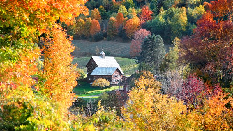 Celeiro no lado do país de Vermont cercado por árvores do outono foto de stock