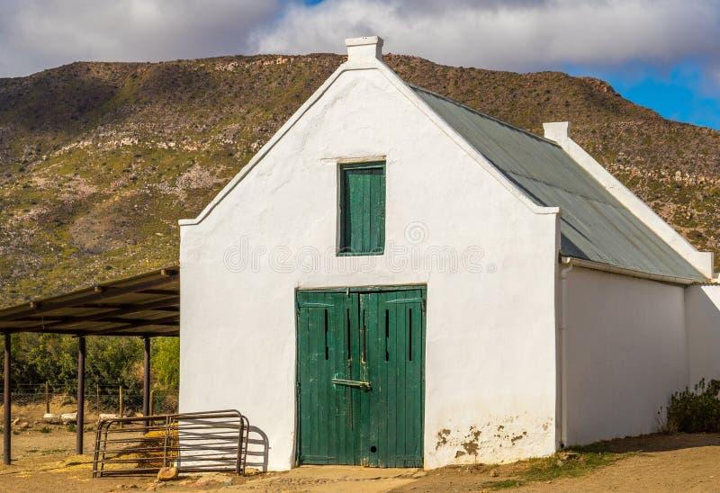 Celeiro velho com as portas de madeira verdes e uma montanha no fundo fotografia de stock royalty free