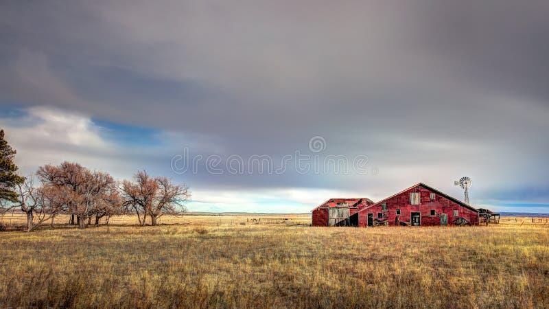 Celeiro vermelho abandonado velho no campo fotografia de stock royalty free