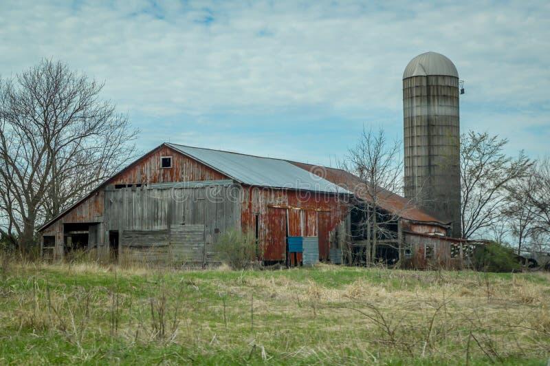 Celeiro vermelho rústico com silo no campo imagem de stock royalty free