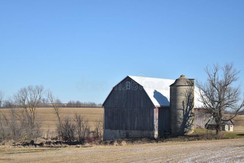 Celeiro vermelho velho com silo em uma exploração agrícola no outono atrasado em um dia ensolarado imagem de stock