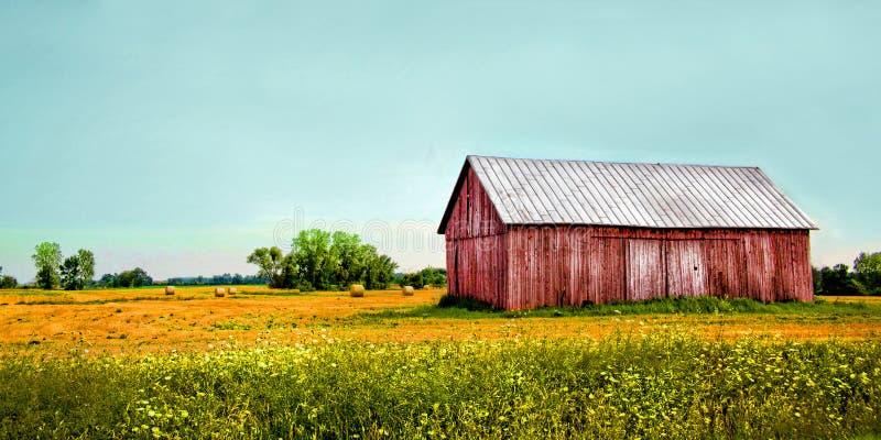 Celeiro vermelho velho em um campo com o céu azul do aqua imagens de stock royalty free