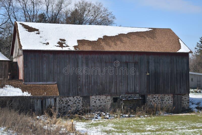 Celeiro vermelho velho no inverno adiantado com apenas um toque da neve em um dia ensolarado em uma exploração agrícola imagem de stock