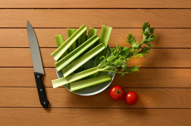 Celery cut with tomato and knife beside royalty free stock image