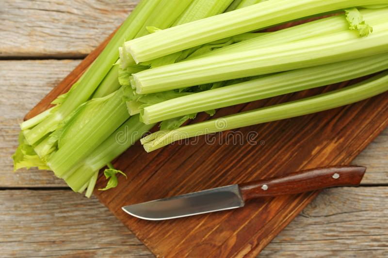 Celery with knife. Celery on cutting board with knife stock photo