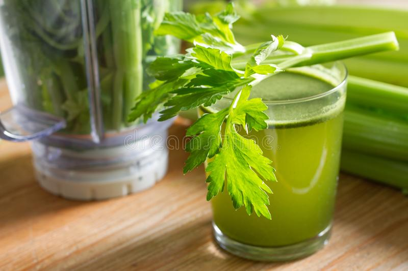Celery juice healthy life stile and blender on wooden board. Green energy royalty free stock images