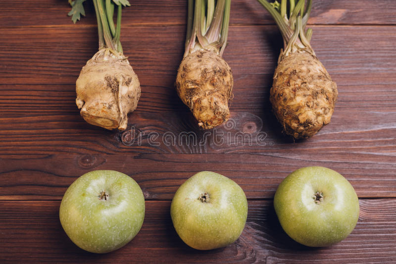 Celery with roots and leaves and green apples on the wooden table royalty free stock image