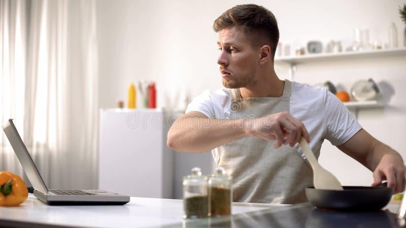 Celibe che prepara pasto in pentola, leggente ricetta e cucinante le punte online, corsi fotografia stock