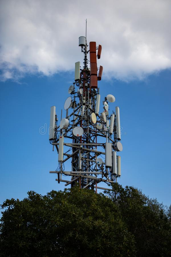 Cell antenna over the tree with cloudy sky stock photography