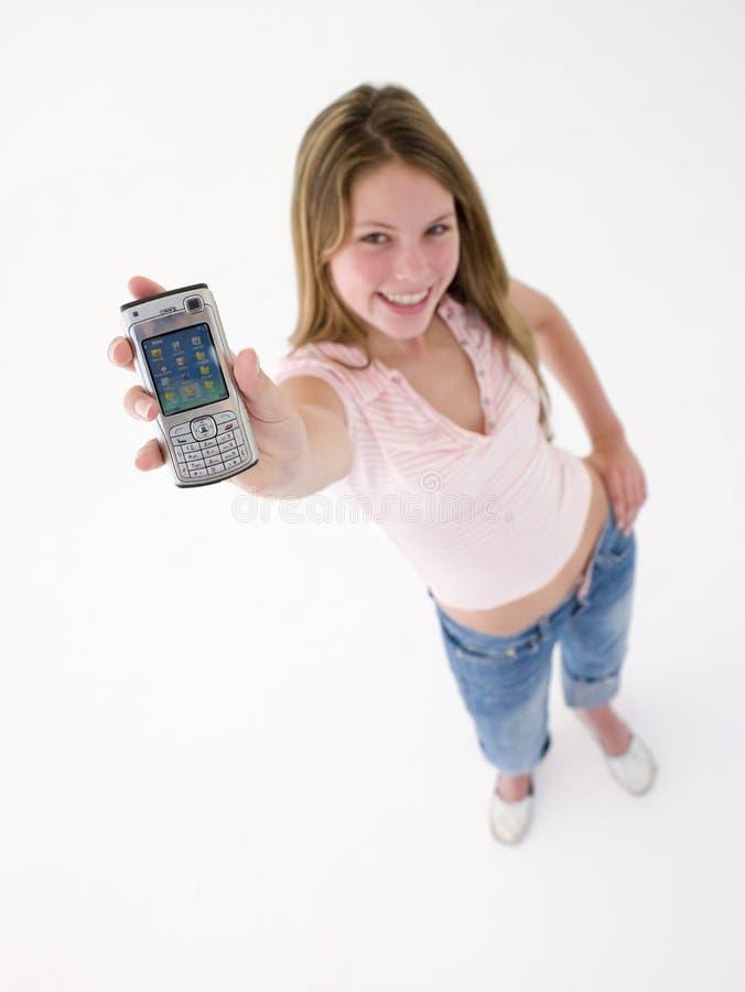 cell- flickaholdingtelefon som ler tonårs- övre arkivfoto