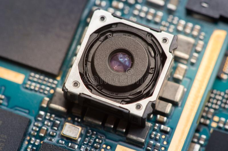 Cell phone camera module with other parts of device, service and repair concept. Blue printed circuit board royalty free stock photography
