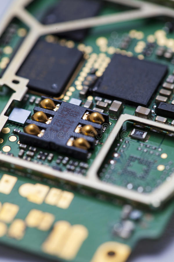 Cell phone circuit board with electronic elements. Macro shot of a cell phone processor board stock photo