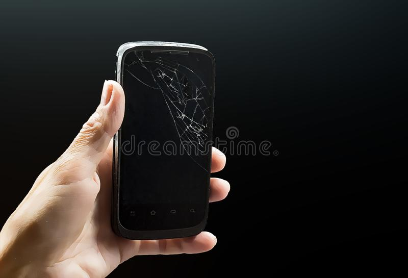 Cell phone with cracked glass. On a black background. In the hand is a smartphone with a broken black screen royalty free stock photo
