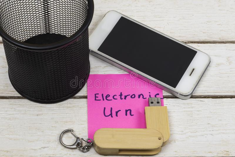 Cell phone and flash drive near trash can with the words: Electronic Urn royalty free stock photo