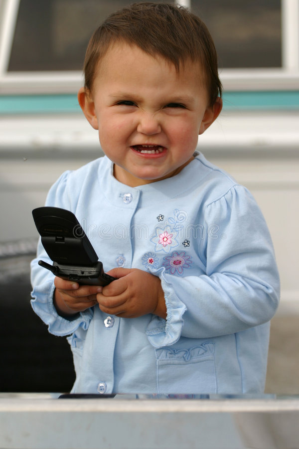 Cell Phone Frustration. Baby girl with cellular phone and a priceless expression that can be either frustration or somewhat thrilled. Dropped call? No bars? Bad royalty free stock images