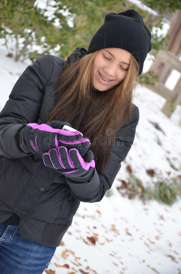 Cell phone and gloves. Teenage girl trying to use her phone outside in the cold with big winter gloves stock photography