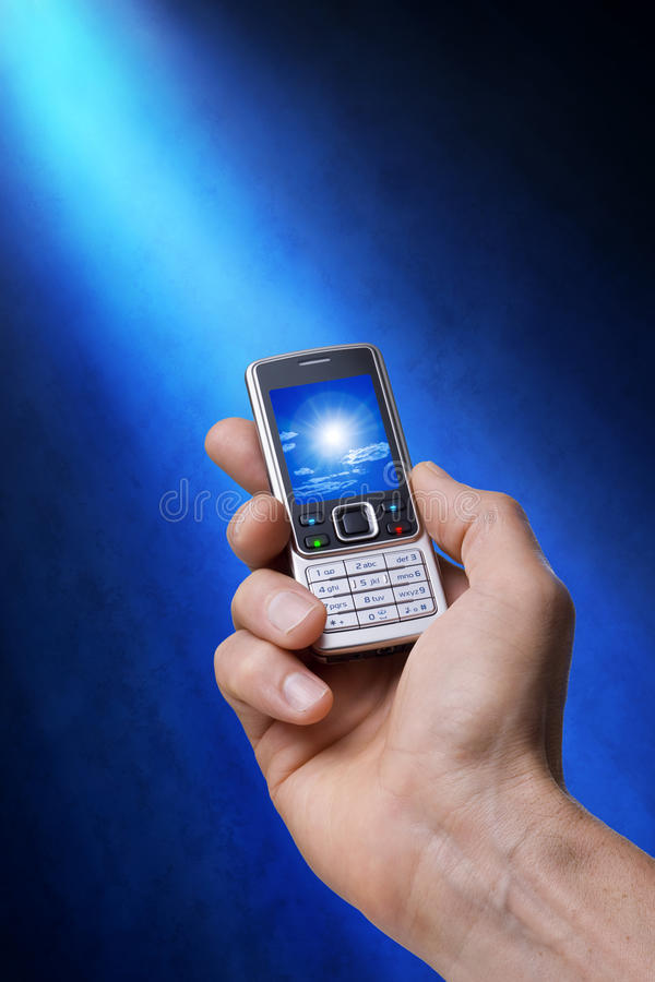 Cell Phone in Hand with Photo. A cell phone being held in a mans hand under a blue beam of light with sky photo on the screen royalty free stock photo