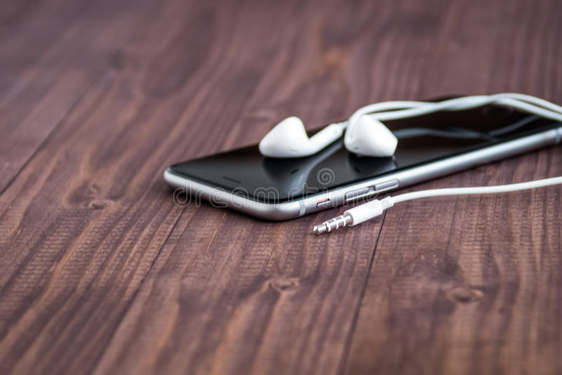 Cell phone and headphones lay on an old wooden table stock photography