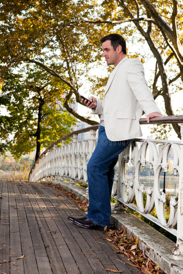 Cell Phone Man. A man checking his cell phone in a park stock photos