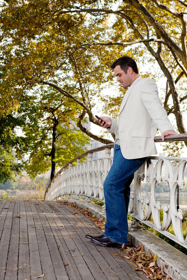 Cell Phone Man. A man checking his cell phone in a park stock images