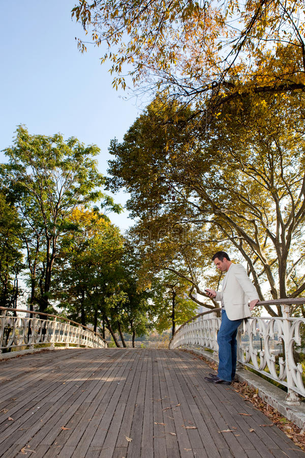 Cell Phone Man Park. A man checking his cell phone in a park stock photography