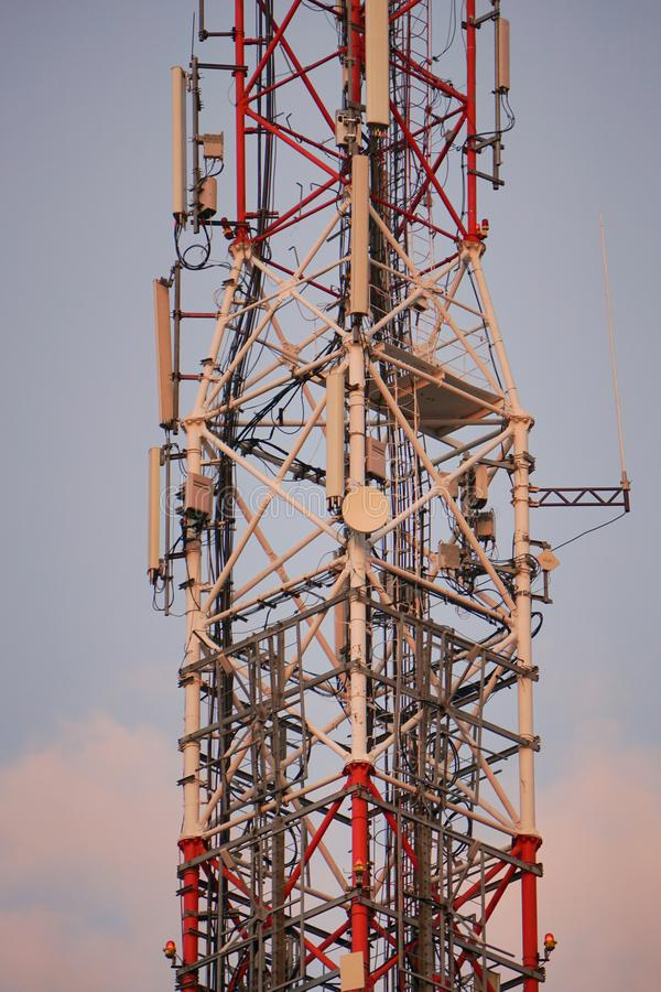 Cell phone and microwave atenna tower. Lattice telecommunication tower with microwave and GSM antennas at sunset royalty free stock images