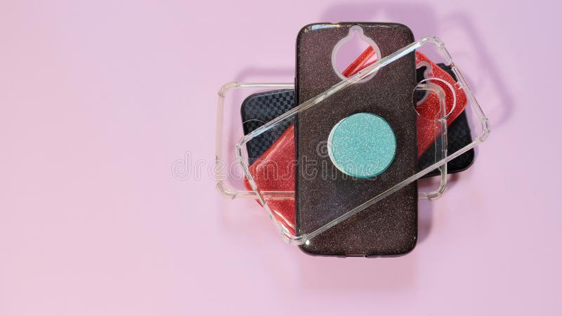Cell phone, mobile case in a pink background. Cases it`s important to protect devices from falling down. Cell phone, mobile case in a black background. Cases it` royalty free stock photo
