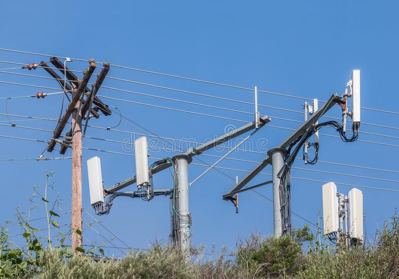 Cell phone monopole towers and power pole. Blurred foreground foliage. Blue sky background royalty free stock images