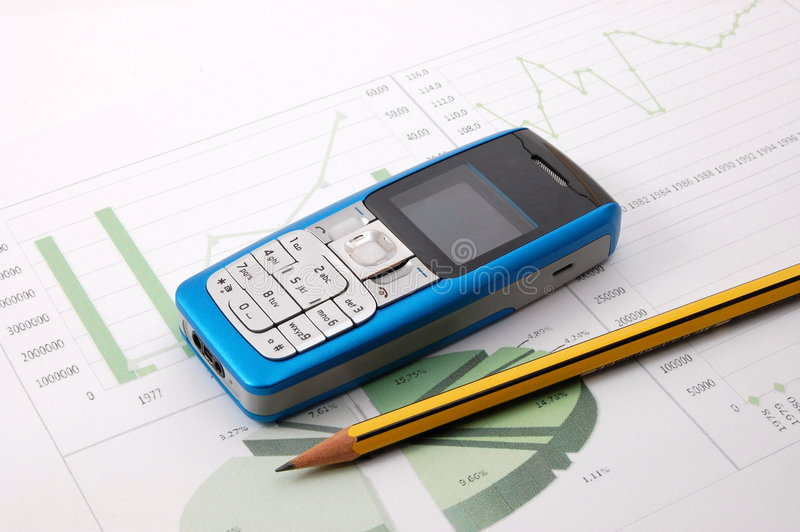 Cell phone over business chart stock photography
