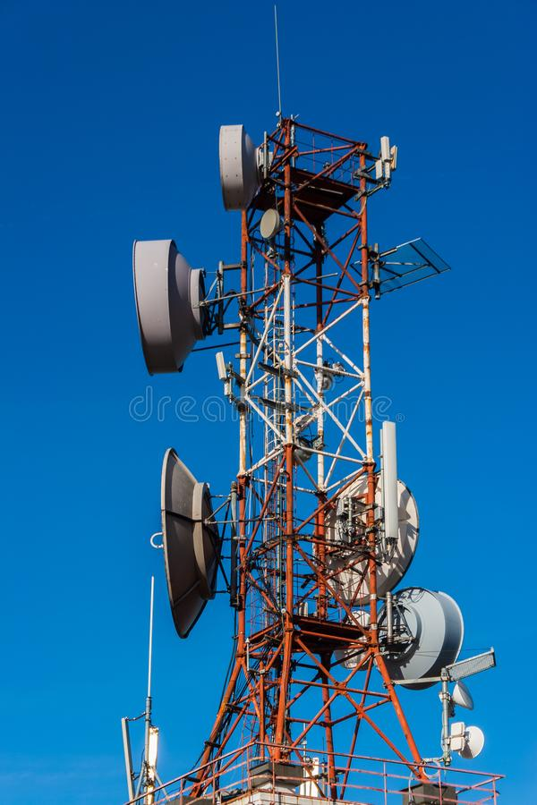 Cell phone relay tower in a bright sunny day. Clear blue sky in stock images