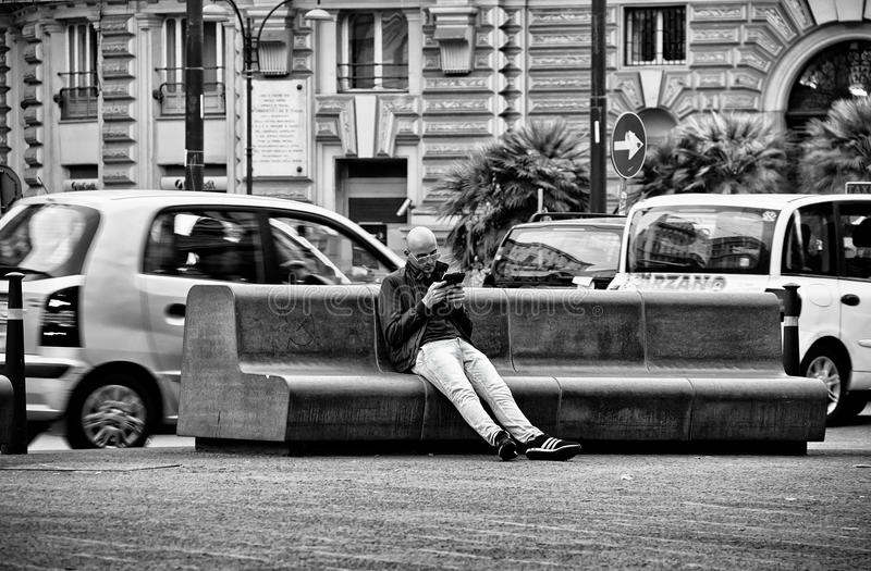 Cell Phone Talking. Man Sitting in Park in Historical City Center of Naples,Italy stock photo