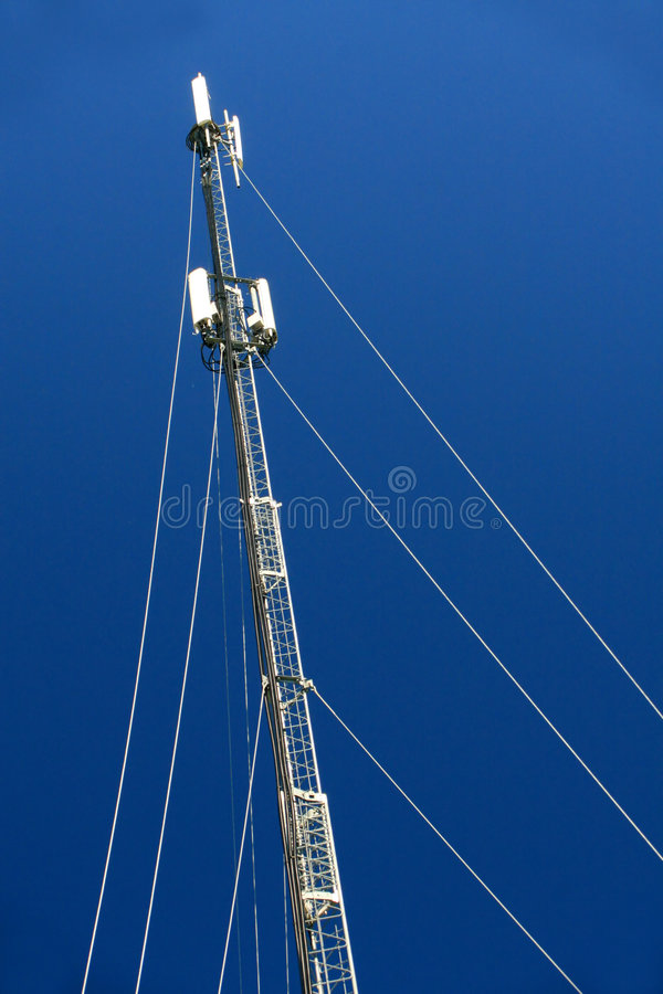 Cell Phone Tower. A multi-antenna cell phone tower against a deep blue sky royalty free stock images