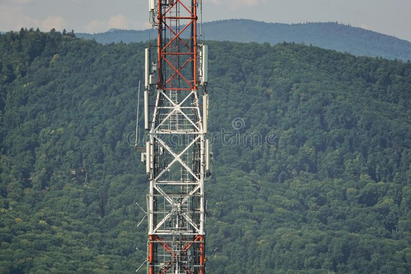 Cell phone tower. Tall lattice telecommunication tower with microwave and GSM antennas on a mountain in Piatra-Neamt royalty free stock photo