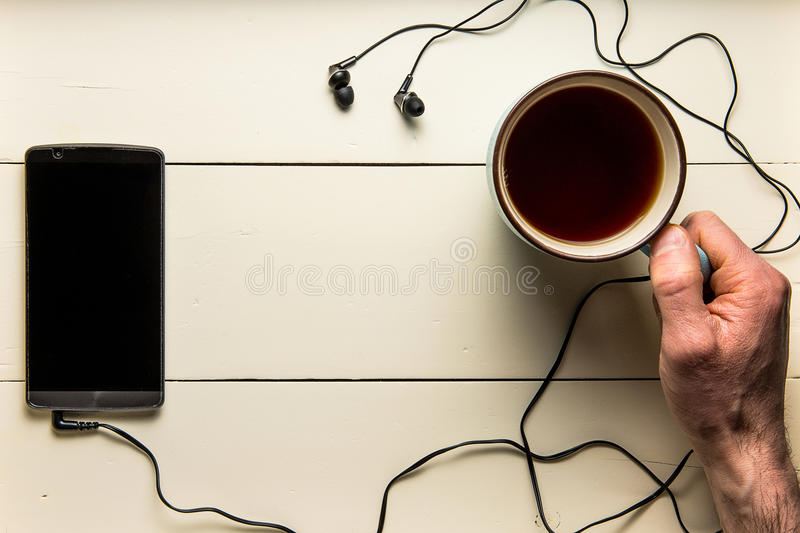 Cell phone on wood with heeadphones and coffee royalty free stock images
