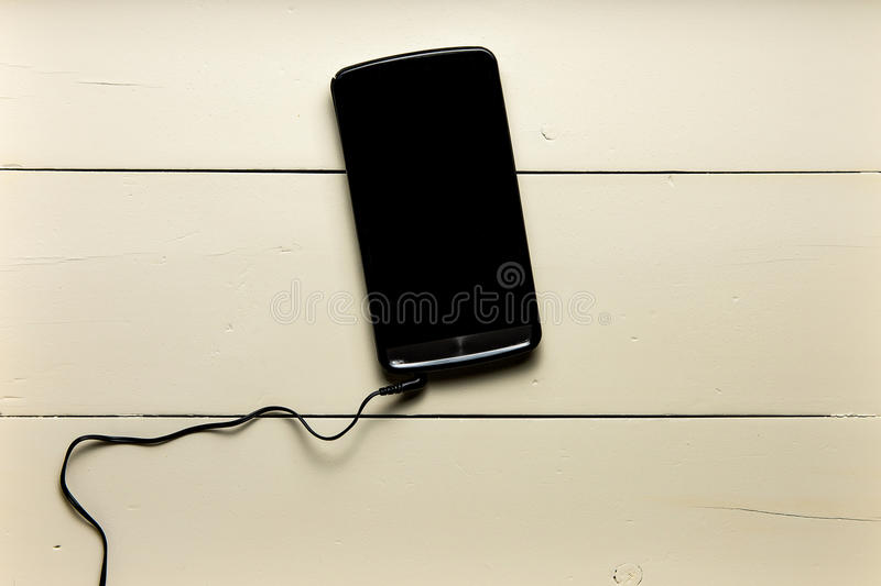 Cell phone on wood with heeadphones royalty free stock photography