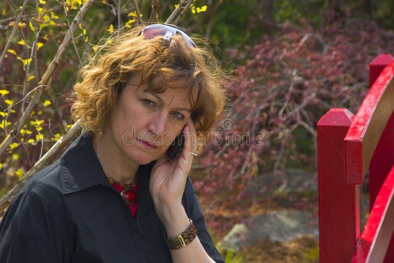 cell som ser den allvarliga kvinnan för telefon royaltyfria bilder