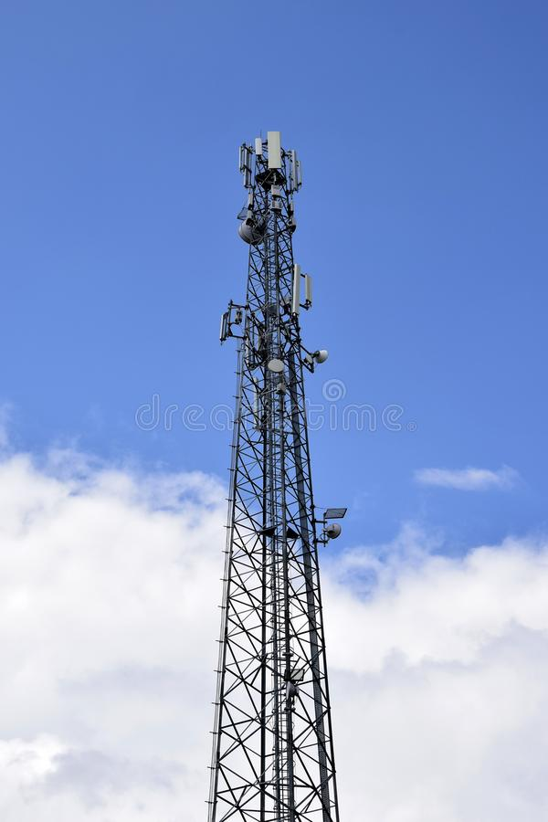 Cell tower against blue sky with clouds. Wireless communication. stock photography
