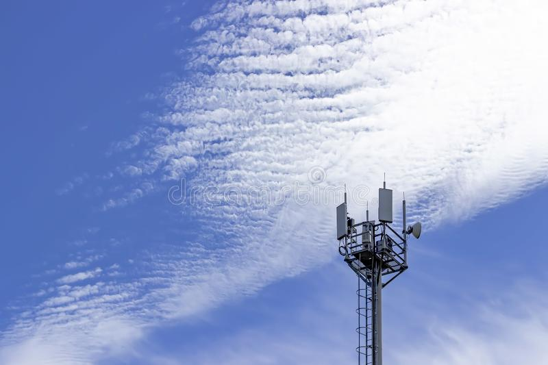 Cell tower on a background of blue sky and clouds. Communication technology. Telecommunication industry. Mobile or telecom network. 4g, satellite, white royalty free stock images