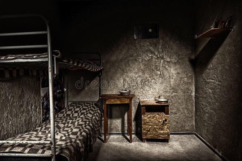 Cella vuota scura con il letto di cuccetta del ferro ed il comodino di legno fotografia stock libera da diritti